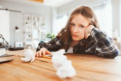 сердитая и утомленная девушка ребенка имея проблемы с домашней работой, бросая бумаги с ошибками стоковые фотографии rf