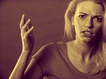 Сердитая, сотрясенная белокурая женщина показывать руки Стоковое фото RF