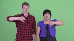 Сердитые молодые multi этнические пары давая большие пальцы руки вниз совместно сток-видео