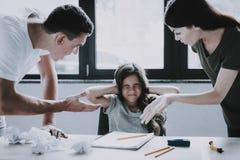 Сердитые родители выкрикивают на девушке пока делать домашней работы стоковые фотографии rf