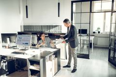 Сердитый бизнесмен браня его ленивую секретаршу для не завершать задачи стоковое фото