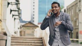 Сердитый бизнесмен смешанной гонки имея онлайн видео- болтовню в бизнес-конференции используя smartphone Стоковые Изображения RF