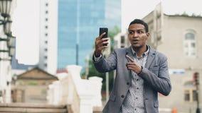 Сердитый бизнесмен смешанной гонки имея онлайн видео- болтовню в бизнес-конференции используя smartphone Стоковые Фотографии RF