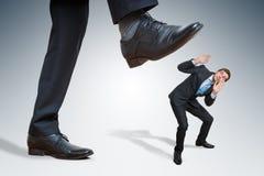 Сердитый большой бизнесмен злоупотребляет малым работником стоковое фото