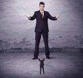 Сердитый большой менеджер смотря человека мелкого бизнеса Стоковые Изображения RF