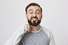 Сердитый бородатый показ парня я отрежу вас возглавляю жест с указательным пальцем над шеей, стоя над серой предпосылкой I стоковое фото rf