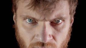 Сердитый взгляд молодого человека в студии на черной предпосылке акции видеоматериалы