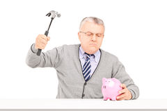 Сердитый возмужалый человек пробуя сломать piggy банк с молотком Стоковая Фотография