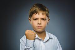Сердитый мальчик изолированный на серой предпосылке Стоковое Изображение