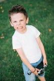 Сердитый мальчик с гримасой на его стороне держа камеру фильма Стоковые Фотографии RF