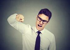 Сердитый молодой бизнесмен обвиняя кто-то стоковое изображение rf
