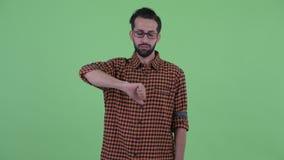 Сердитый молодой бородатый персидский человек хипстера давая большие пальцы руки вниз акции видеоматериалы