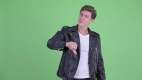 Сердитый молодой воинственно настроенный человек давая большие пальцы руки вниз видеоматериал