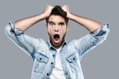 Сердитый молодой человек кричащий над серой предпосылкой Стоковые Фотографии RF