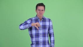 Сердитый молодой человек хипстера давая большие пальцы руки вниз видеоматериал