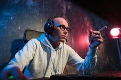 Сердитый молодой gamer в стеклах играя игру на компьютере используя наушники стоковое изображение