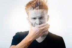 Сердитый напряжённый человек держа руку около рта и смотря прямо Стоковое Изображение