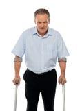Сердитый постаретый человек при костыли смотря вас Стоковая Фотография
