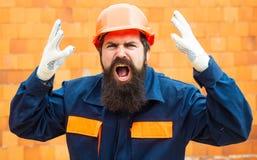 Сердитый построитель Случай на строительной площадке Правила техники безопасности для построителей Бородатый человек в шлеме на к стоковые фотографии rf