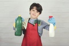 Сердитый ребенок с чистящими средствами стоковое изображение