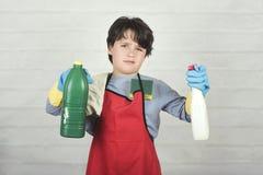 Сердитый ребенок с чистящими средствами стоковая фотография