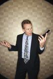 сердитый сотовый телефон бизнесмена Стоковая Фотография RF