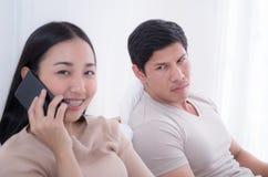 Сердитый супруг на жене кровати игнорирует но только принимает на телефон стоковая фотография rf