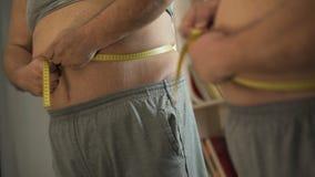Сердитый человек при проблемы веса измеряя его талию перед зеркалом сток-видео