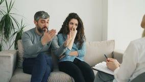 Сердитый человек споря и говоря о его жене к советнику замужества Молодые пары навещая профессиональный психолог акции видеоматериалы