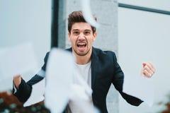 Сердитый яростный мужской работник офиса бросая скомканную бумагу, имеющ нервное расстройство на работе, кричащей в гневе, стресс стоковое фото rf