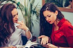 2 сердитых друз сидя в кафе и обсуждая отрицательный письменный текст в газетах стоковые изображения