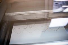 Сердца вырезывания гравировального станка лазера от бумаги стоковые изображения