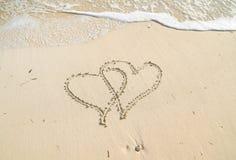 Сердца в песке с прибоем стоковые изображения