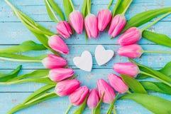 Сердца дня или свадьбы валентинок обрамленные с розовыми тюльпанами цветут на предпосылке бирюзы деревянной Стоковая Фотография