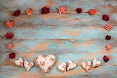 Сердца и вянуть розы на деревянной предпосылке Стоковое Фото