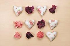 Сердца и вянуть розы на пастельной деревянной предпосылке Стоковые Изображения
