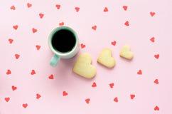 Сердца печенья и кофейная чашка на розовой предпосылке с красными сердцами Стоковое фото RF