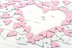 Сердца пинка и белых маленькие на деревянной предпосылке Стоковая Фотография