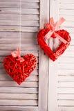 Сердца ротанга вися на белых деревянных жалюзи Концепция торжества дня валентинок Стоковые Фотографии RF