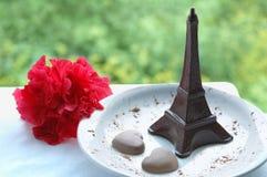 Сердца шоколада и Эйфелева башня шоколада на белой плите На таблице снаружи стоковые фотографии rf