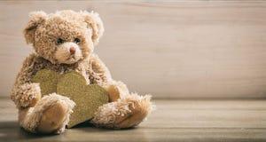 Сердца holdimg плюшевого медвежонка на деревянном поле Стоковые Изображения RF