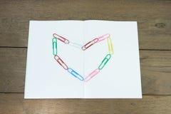 Сердце бумажных зажимов на пустой книге Стоковые Фото