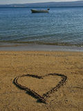 Сердце в песке, шлюпка на море Стоковая Фотография