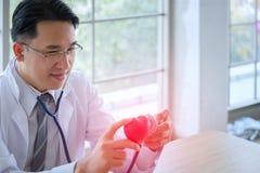 Сердце в руках доктора с стетоскопом который посредничает h Стоковые Фотографии RF