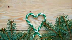 Сердце зеленых конусов конфеты и ветвей рождественской елки на коричневой деревянной предпосылке с космосом бесплатной копии Новы Стоковые Изображения