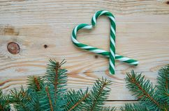 Сердце зеленых конусов конфеты украшенных с ветвями рождественской елки на коричневой деревянной предпосылке Еда дня Нового Года  Стоковое Изображение