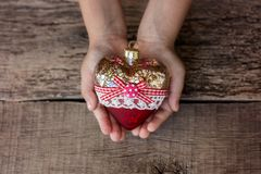 Сердце игрушки рождественской елки в руках ребенка Новый Год Рождество Деревянная предпосылка Стоковая Фотография RF
