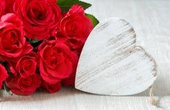 Сердце и букет красных роз на деревянной доске, предпосылке дня валентинок Стоковое Изображение
