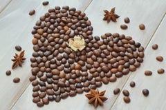 Сердце кофейных зерен со звездой анисовки и сатинировки в пастельных тенях розы на светлой деревянной предпосылке стоковые изображения