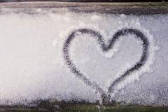 Сердце нарисованное в древесину которая имеет снег на ем стоковая фотография rf